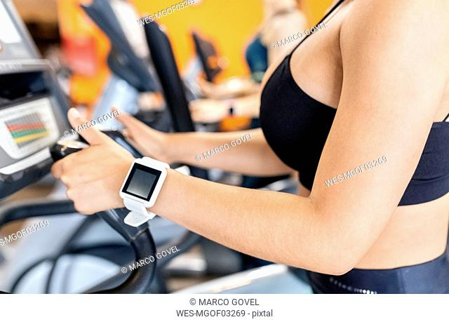 Woman in gym with smartwatch using an elliptical trainer