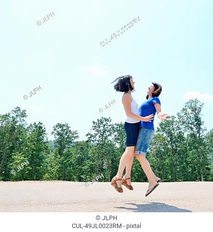 Women jumping together outdoors