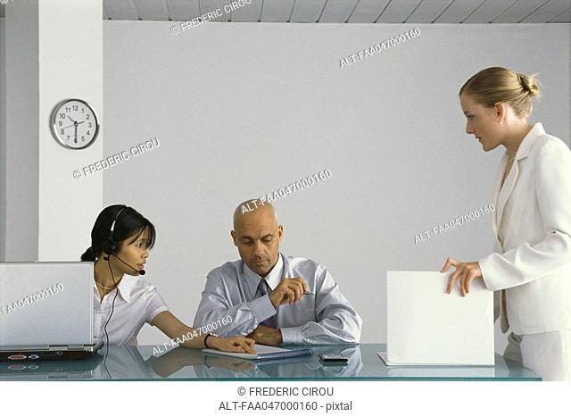 Three business colleagues collaborating in office