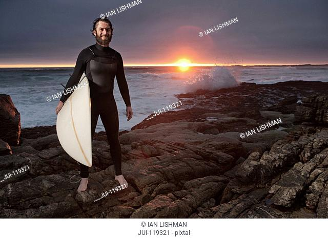 Surfer with surfboard standing on rocks wearing wetsuit with ocean in background and dramatic sunset sky