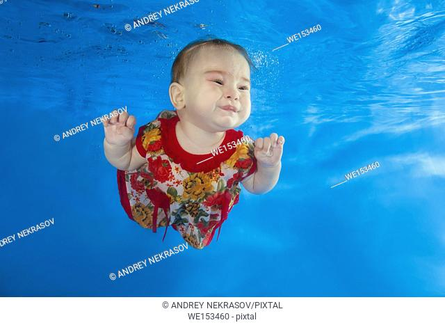 A little girl in a bright dress swims under water in the pool
