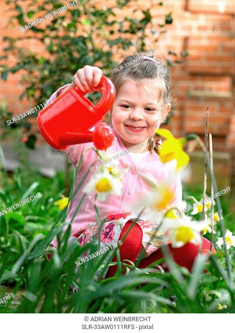 Girl watering flowers in backyard