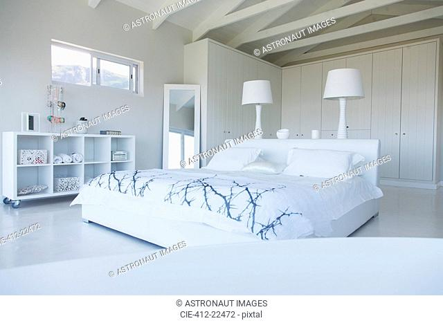 Modern white bedroom interior with double bed