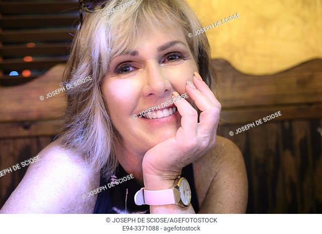 A 60 year old blond woman smiling at the camera in a relaxed setting