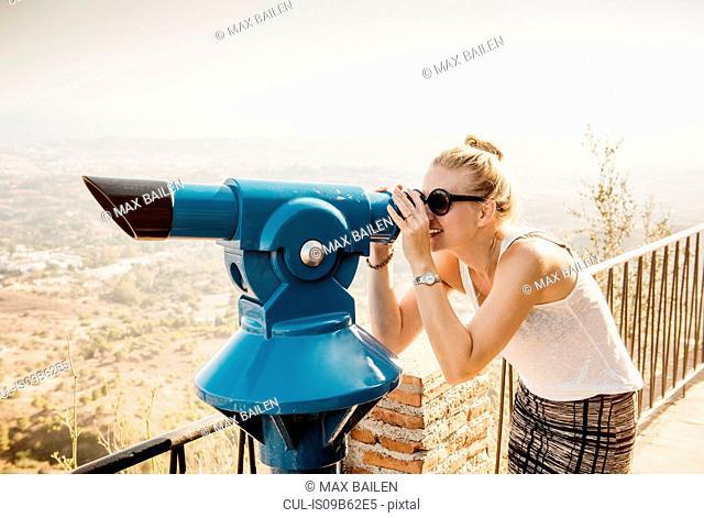 Woman using telescope on viewing platform, Mijas Pueblo, Andalucia, Spain