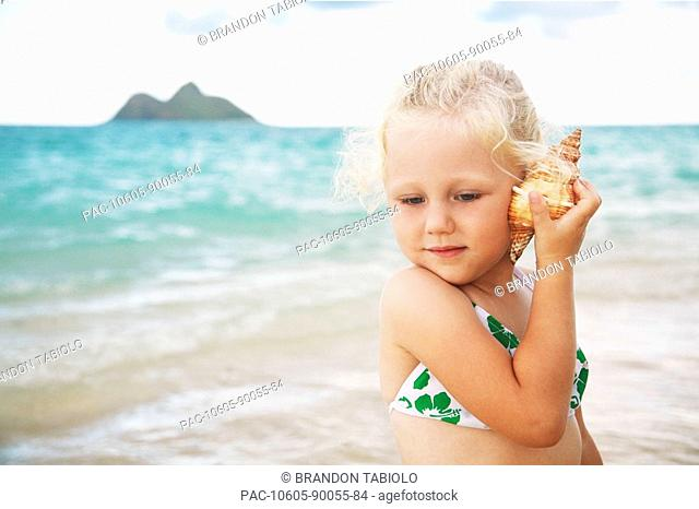 Hawaii, Oahu, Lanikai, Young girl listening to a shell