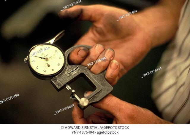 close up of factory worker's hands holding an analogue micrometer
