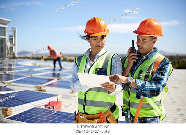 Engineers using walkie-talkie and digital tablet at solar power plant