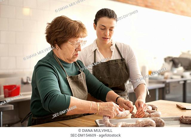 Women tying sausages