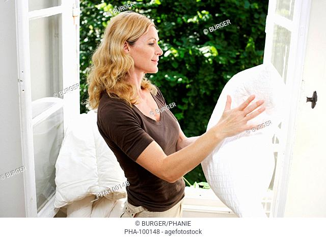 Woman cleaning pillow by the window