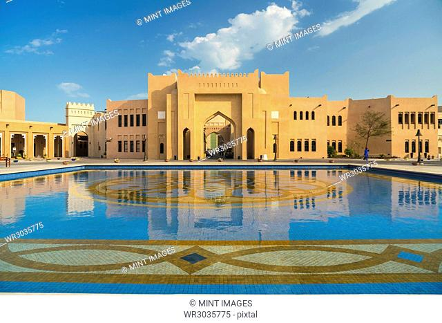 Facade of Middle Eastern building, pond with blue and golden mosaic tiles in foreground