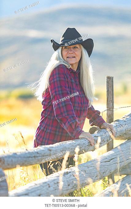 Mature woman wearing cowboy hat in field
