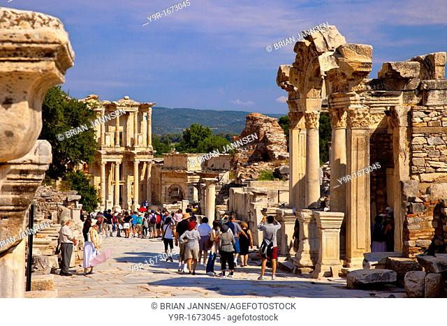 Tourists crowd the Street of Curetes below the Temple of Hadrian with Library of Celsus beyond in ancient Ephesus, near Selcuk Turkey