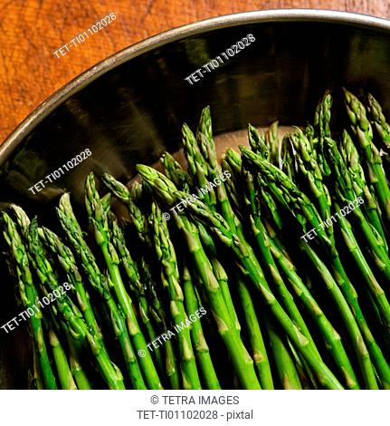 Green asparagus in metal pot