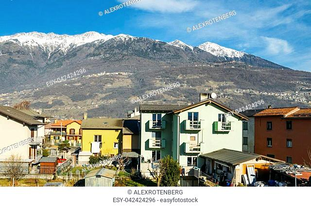 Residential buildings on foreground with majestic Italian alps in background, captured near Sondrio in Valtellina, Italy