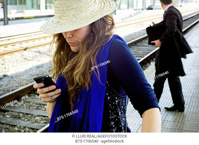 mujer joven mirando el telefono movil en la estacion de tren de Girona, Cataluña, España, Young woman looking at mobile phone on the train station in Girona