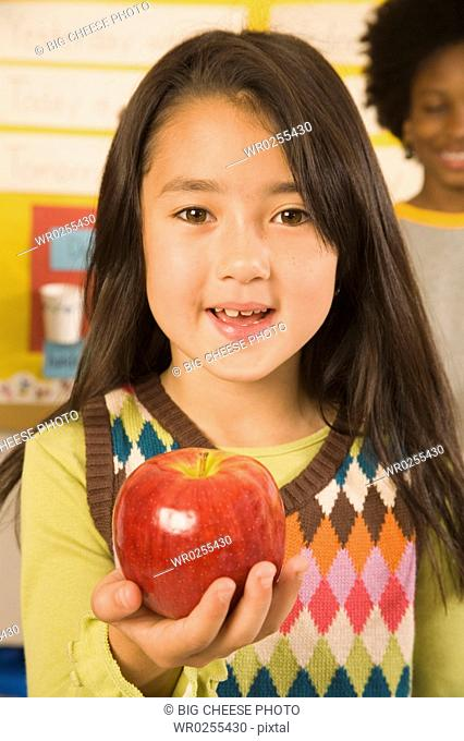Portrait of girl holding apple in classroom