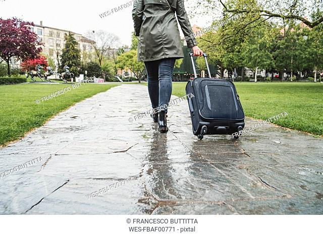 Young woman walking in city park on a rainy day