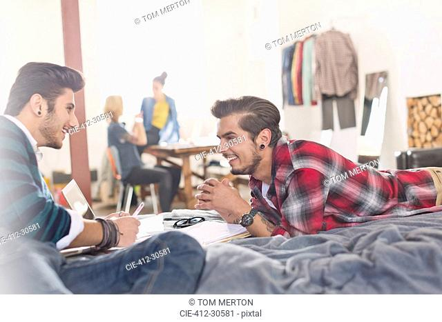 College students studying on bed in apartment