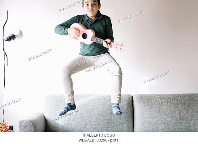 Portrait of boy with ukulele jumping in the air on the couch