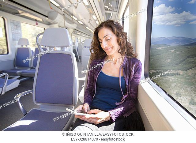 brown hair smiling woman dressed in purple and blue, sitting traveling by train typing on mobile smart phone