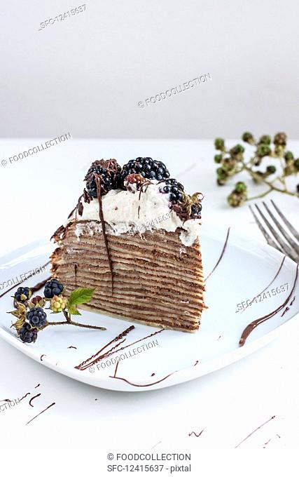 A slice of pancake cake with chocolate and blackberries