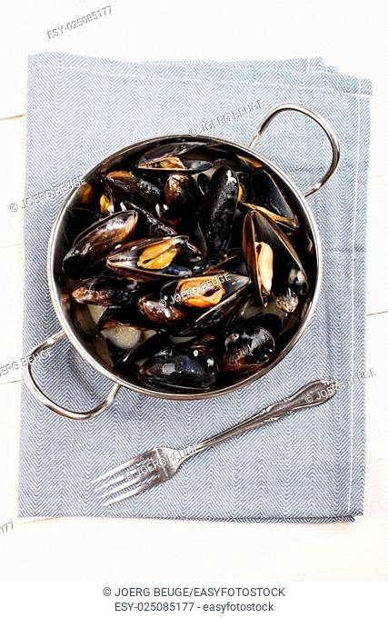 boiled scottish mussels in a metal bowl and fork on a light blue cloth