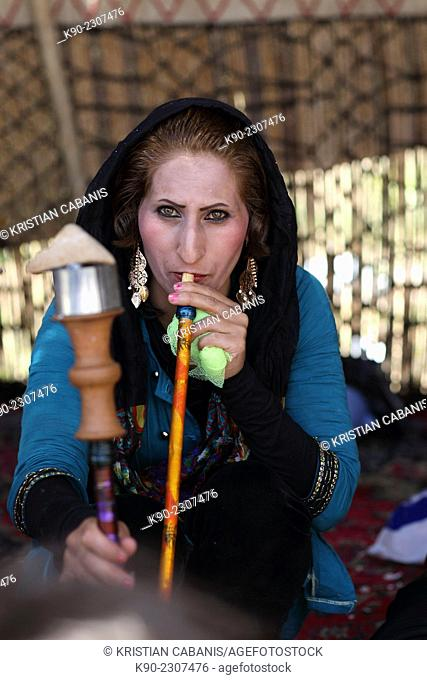 Nomadic woman in colorful dress smoking a pipe during a wedding ceremony sitting in a tent, Zagros mountains, Central Iran, Asia