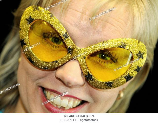 A blonde lady laughing, wearing a carneval mask