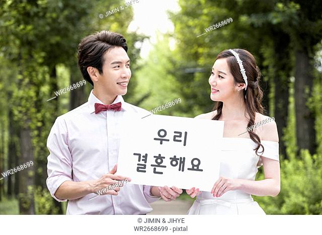 Portrait of young wedding couple smiling with Korean message at each other outdoors