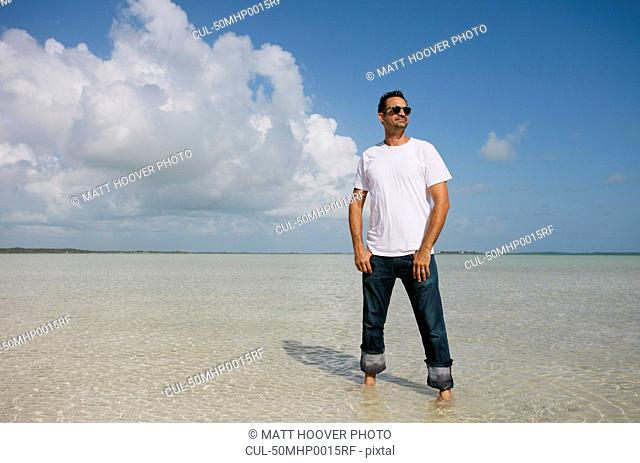 Man standing in water on tropical beach