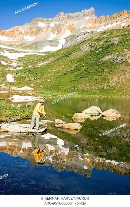 Man fishing in alpine lake