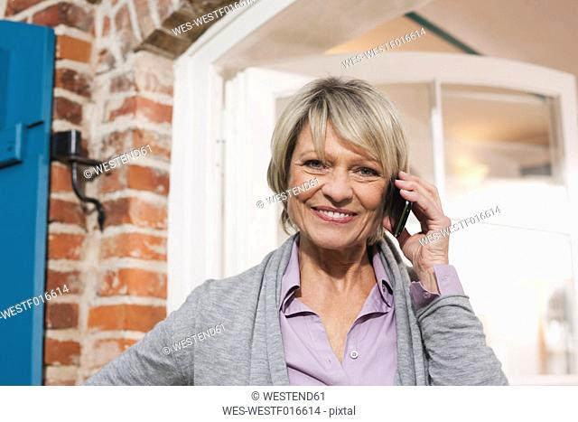 Germany, Kratzeburg, Senior woman with cell phone, smiling, portrait