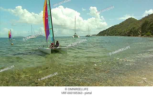 Two people landing small sailing Catamaran ashore on white sandy beach