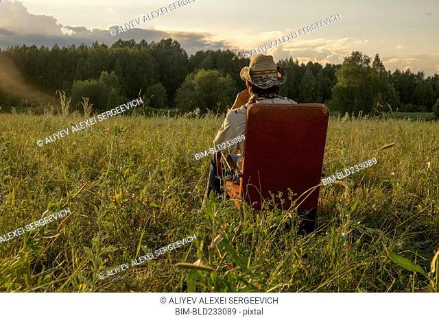 Mari man sitting on chair in field