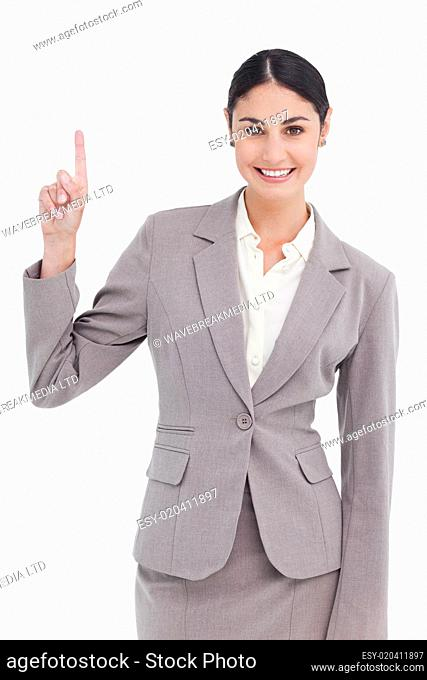 Smiling young businesswoman pointing up