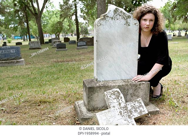 A Young Woman Visits A Tombstone In A Cemetery; Edmonton, Alberta, Canada