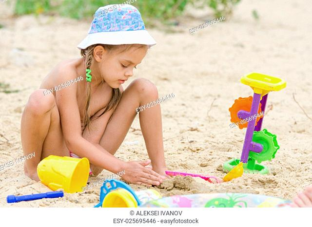 Funny five-year girl playing with sand molds on the beach