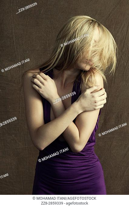 Slim young blond woman hair covering face