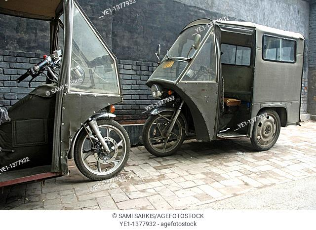 Two parked motor tricycles against a grey brick wall, Hutong district, Beijing, China