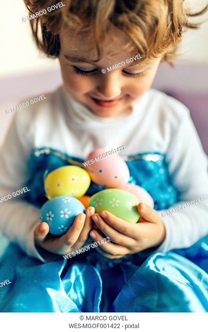 Happy little girl holding Easter eggs