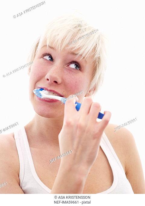 A Scandinavian teenage girl brushing her teeth