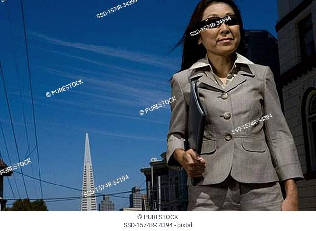 Businesswoman holding a file and smirking, San Francisco, California, USA