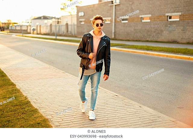 Handsome young man with a hairstyle in sunglasses in a leather jacket, jeans and white sneakers on the street at sunset