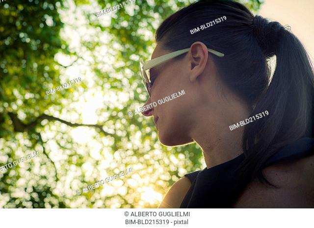 Low angle view of Caucasian woman standing under tree