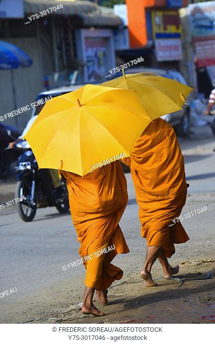 Buddhist monks under umbrella on the street of Phnom Penh, Cambodia, South East Asia, Asia