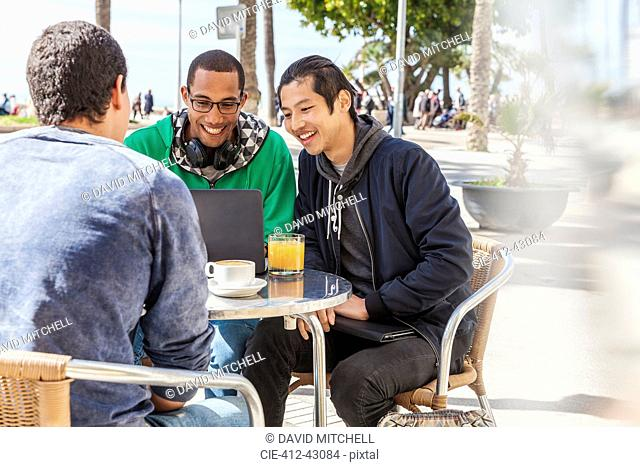 Male friends using laptop at sunny sidewalk cafe