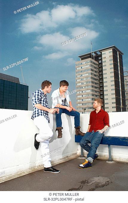 Men talking on urban rooftop