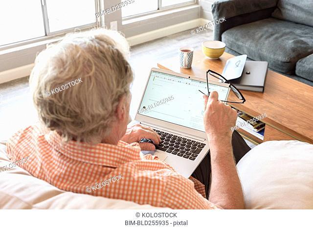 Caucasian man holding eyeglasses using laptop