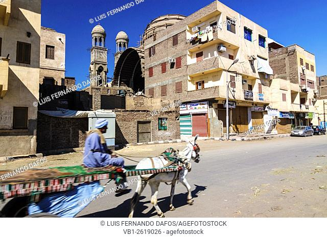Man in a donkey cart passing by the still in construction new Coptic cathedral of Luxor, Egypt
